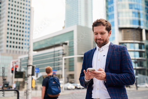 Foto  Smiling businessman standing in the city sending text messages