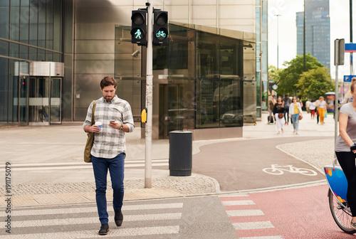 Fotografia Young man walking through the city using a cellphone