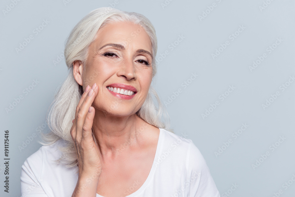 Fototapety, obrazy: Charming, pretty, old woman touching her perfect soft face skin with fingers, smiling at camera over gray background, using day, night face cream, cosmetology procedures