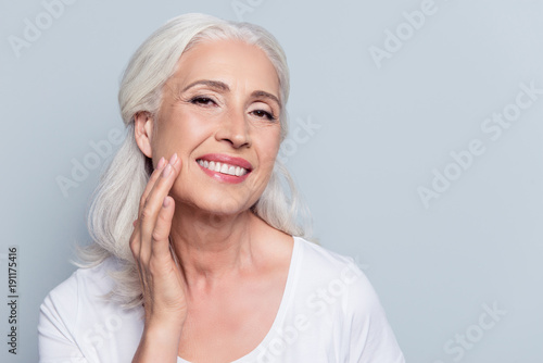 Fotografía  Charming, pretty, old woman touching her perfect soft face skin with fingers, sm