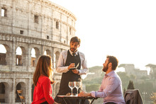 Elegant Waiter Writing Orders On Notebook Serving A Young Happy Couple In Bar Restaurant In Front Of Colosseum In Rome At Sunset