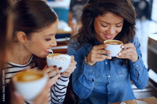 Obraz na płótnie Three young women enjoy coffee at a coffee shop