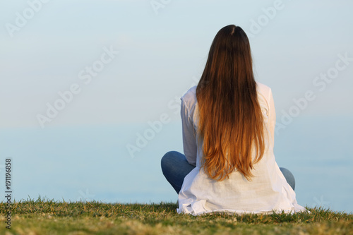 Woman alone watching the sky sitting on the grass