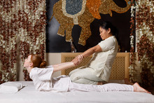 Young Female Receiving Massage By Therapist In Traditional Thai Position
