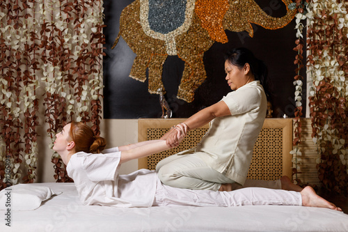 Fototapeta Young female receiving massage by therapist in traditional thai position obraz