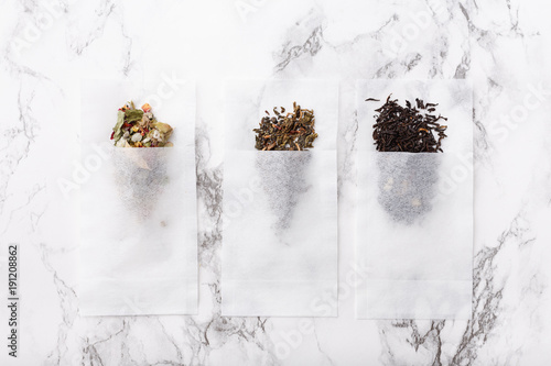 Vászonkép herbal, black, green tea in a sachet on a marble surface