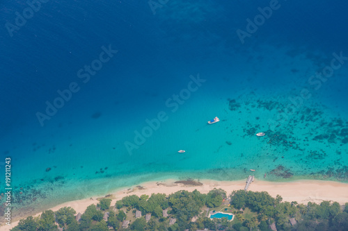 In de dag Luchtfoto The tropical bay with stony beach, boats and buildings, aerial view. Luganville, Espiritu Santo, Vanuatu.