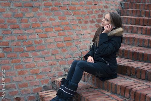 Fotografie, Obraz  Teenage girl talking on the smartphone outside