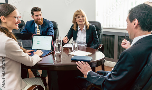 Fototapeta Confident business people smiling while listening to their colleague presenting
