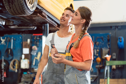 Photo  Two dedicated auto mechanics smiling happy, while checking the modified wheels o
