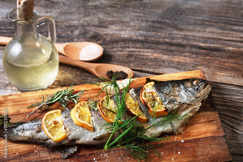 Foto op Aluminium Vis fish on rustic table with fresh ingredients for cooking