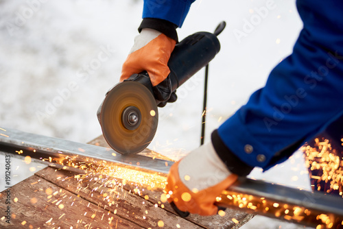 Cropped close up of an industrial worker in protective uniform and gloves cutting metal sawing welding iron outdoors in winter factory industry metalworking electric sparks steel profession.
