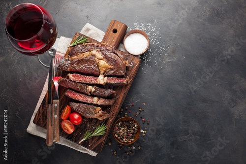 Spoed Foto op Canvas Steakhouse Grilled ribeye beef steak with red wine, herbs and spices on a dark stone background. Top view with copy space for your text