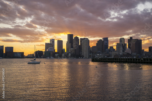 Scenic view of river by cityscape against cloudy sky during sunset