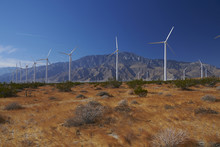 Scenic View Of Windmills On Field Against Mountains And Sky
