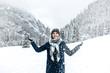 Uśmiechnięta dziewczyna rzuca śniegiem w górach zimą.