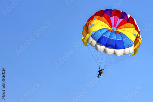 Fotografie, Obraz  Two men are gliding using a parachute on the background of the blue sky