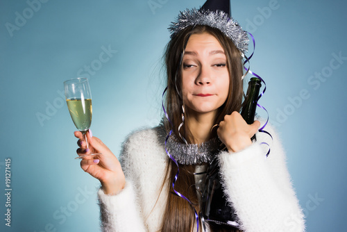 Photo drunk woman in a festive cap holding champagne in hands