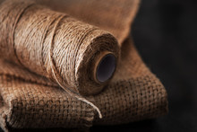 Natural Jute Twine Roll, Burlap On Black Background. Supplies And Tools For Handmade Hobby Leisure