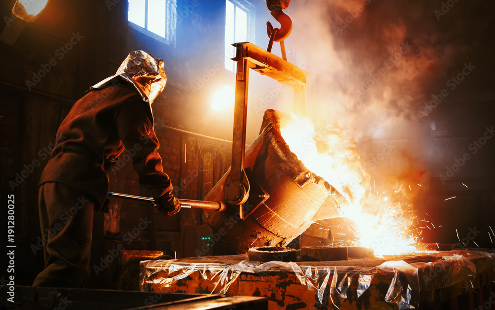 Fototapety, obrazy: Workers operates at the metallurgical plant. The liquid metal is poured into molds. Worker controlling metal melting in furnaces.