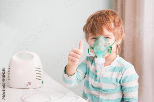 Stampa su Tela Little boy making inhalation with nebulizer at home.