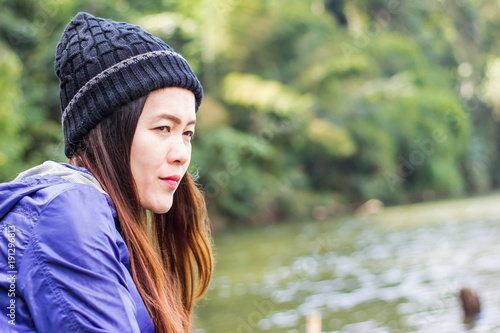 Fotografía  Asian woman wearing a knit cap traveling on holiday alone