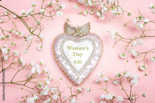 Foto op Canvas Bloemen Women's Day greeting message on decorative heart with gypsophila flowers on pink background.
