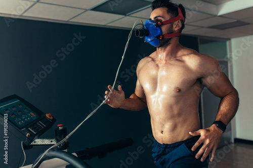Photo  Fit and muscular athlete with mask running on treadmill