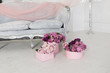 Pink and purple roses in a pink round box standing near the grey sofa. Decoration