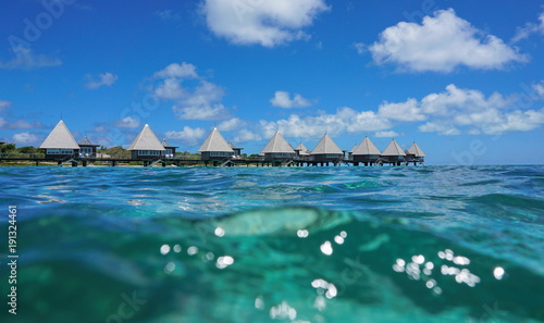 Fotografiet Overwater bungalows in the lagoon seen from sea surface, Maitre island, New Cale