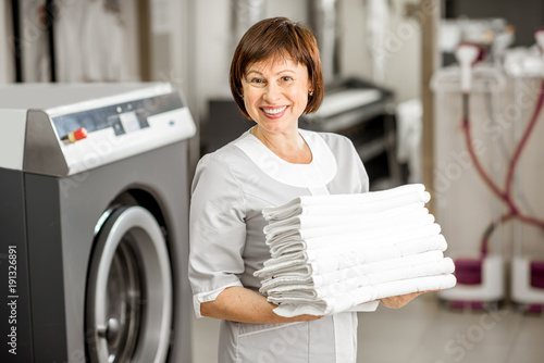 Fotografie, Obraz  Portrait of a senior washwoman in uniform standing with towels in the hotel laun