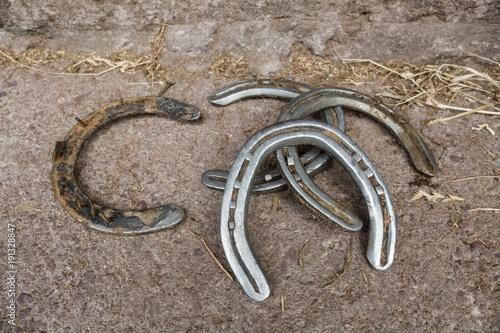 Spoed Foto op Canvas Paardrijden Horseshoe laid on floor in stable