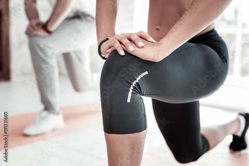 Poster Ontspanning Healthy and strong. Scaled up look on young lady wearing sportswear training her legs and stretching during a gym session.