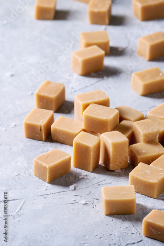 Salted caramel fudge candy over grey texture background. Close up, space