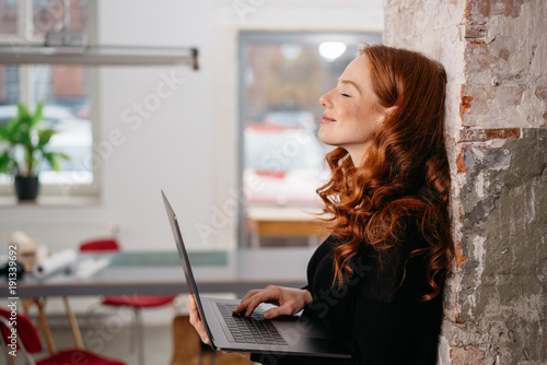 Leinwand Poster Attractive redhead woman standing daydreaming
