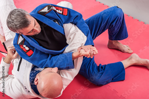 Brazilian jiu jitsu instructor demonstrates ground fighting arm lock techniques
