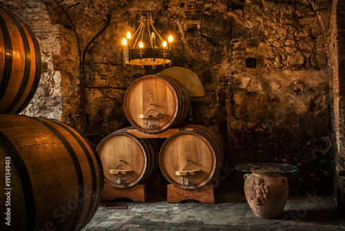 Old Wooden barrels with wine in a wine vault Canvas Print