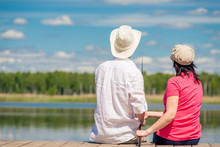 Family Couple With A Fishing Rod Sitting On A Wooden Pier Near The Lake, Rear View