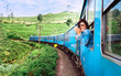 canvas print picture - Happy smiling woman looks out from window traveling by train on most picturesque train road in Sri Lanka