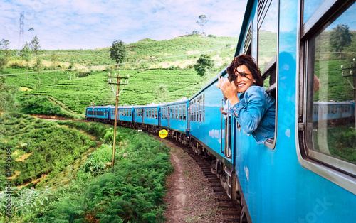 Cuadros en Lienzo Happy smiling woman looks out from window traveling by train on most picturesque
