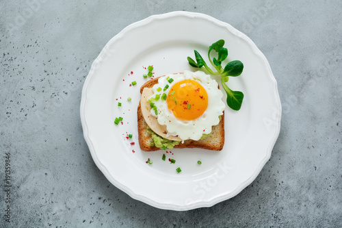Toast with guacamole sauce from avocado, cheese, fried egg and fresh on white ceramic plate on gray concrete background. Selective focus. Top view.