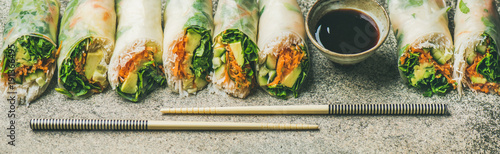 Helathy Asian cuisine. Vegan spring rice paper rolls with vegetables, soy sauce, chopsticks over concrete background. Clean eating, dieting, vegetarian food