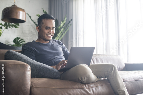 Fotografia  Asian man looking at the computer at home.