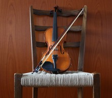Violin With The Bow On A Chair...