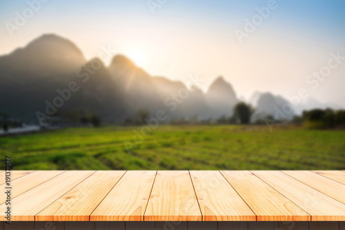 Wood table top with blurred mountain in morning background.