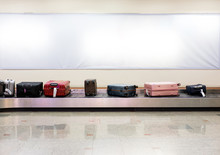 Many Luggages Are Laying Down On The Conveyor Belt At The Airport.
