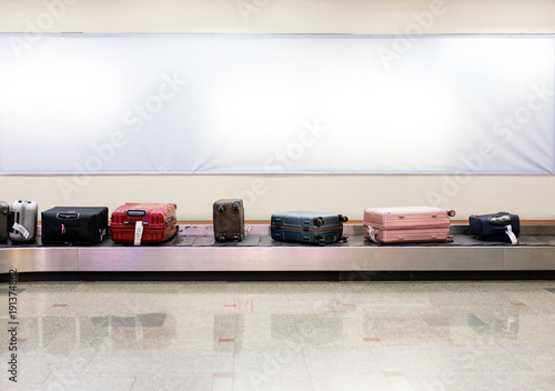 Fotografie, Obraz  Many luggages are laying down on the conveyor belt at the airport