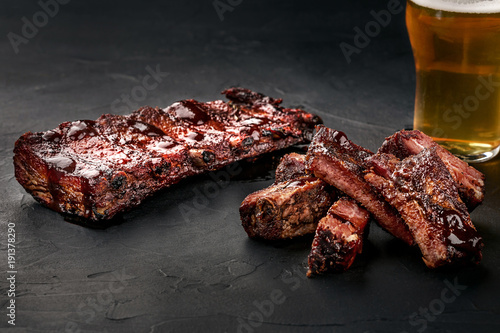 Fotografie, Obraz Pork ribs in barbecue sauce and a glass of beer on a black slate dish