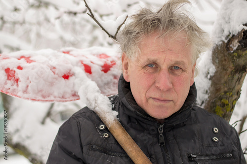 Photo  a funny elderly man with a gray head and toothless cleans snow with a plastic sh