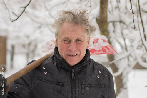 a funny elderly man with a gray head and toothless cleans snow with a plastic sh Poster